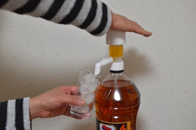 氷の入ったグラスにウイスキーを注ぐ